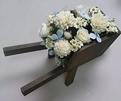 プリザーブドフラワーの白いバラ、一輪車のアレンジメント